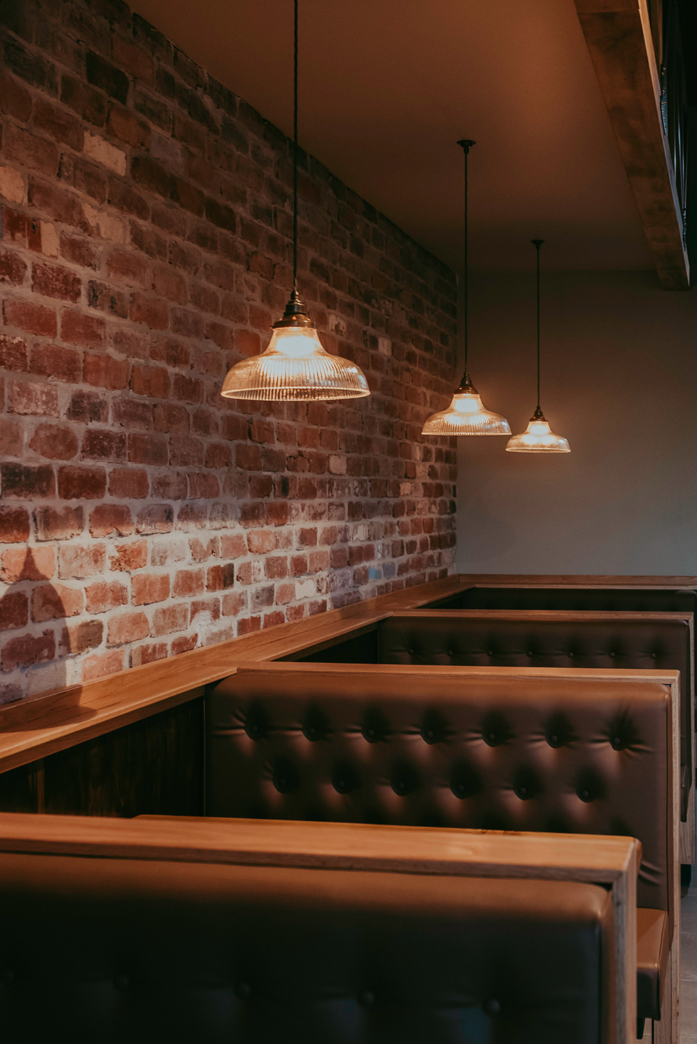 Coffee shop with booth seating and overhanging vintage lights.